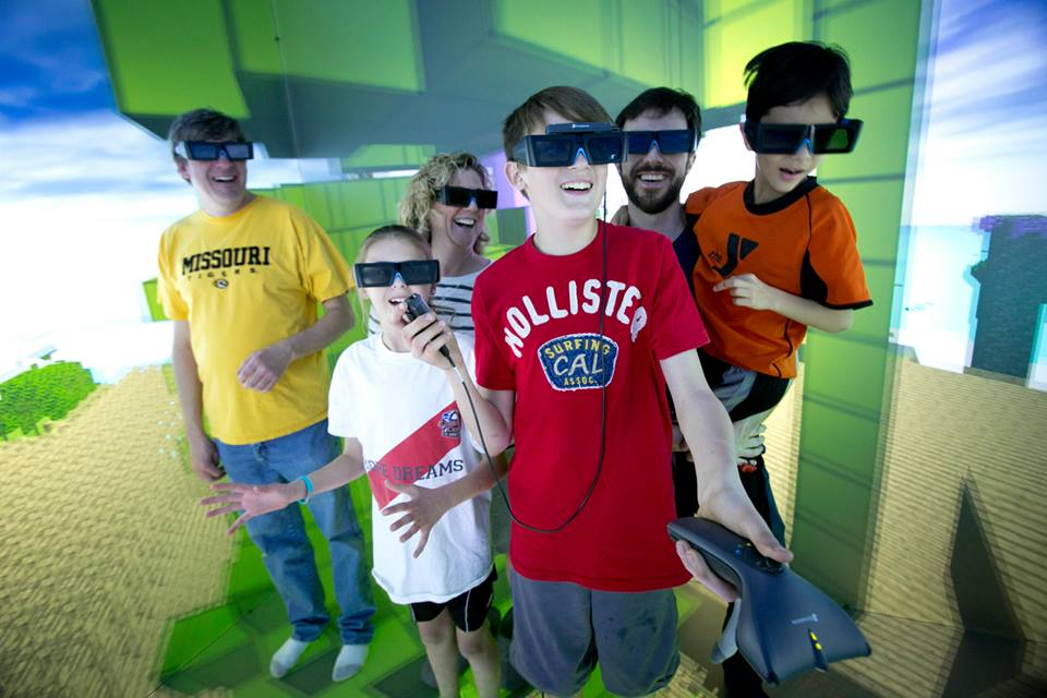A group of Open House visitors explores the six-sided 3D immersive virtual environment of Duke's DiVE.