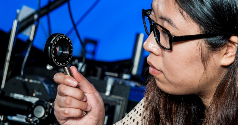 A master's student performs optical research at Duke University.